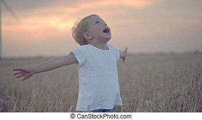 Happy boy in wheat field with wind turbines