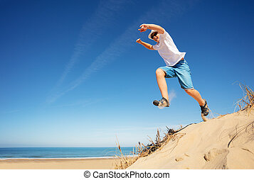 Happy boy in white jump from sand dune on a beach