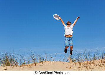 Happy boy jump high on the sand dune holding hat
