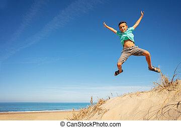 Happy boy jump high on the sand dune raising hands