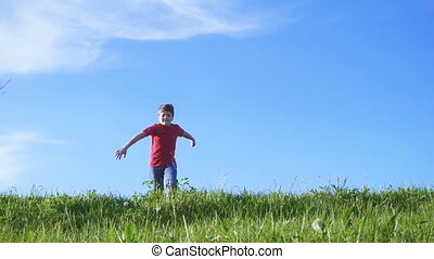 Happy boy jumping on green grass hill