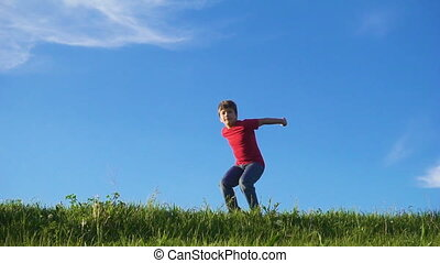 Happy boy jumping on green grass hill against blue sky