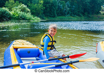 Happy boy kayaking on the river