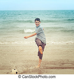 Happy boy kiking a football on the beach