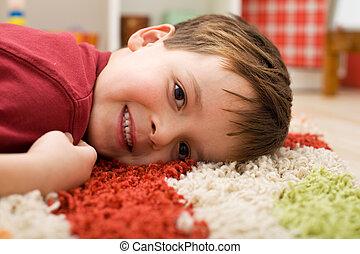 Happy boy laying on a rug