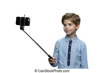 Happy boy making a selfie on white background.