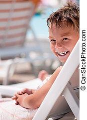 Happy boy on deck chair - Happy boy sitting on a deck chair...