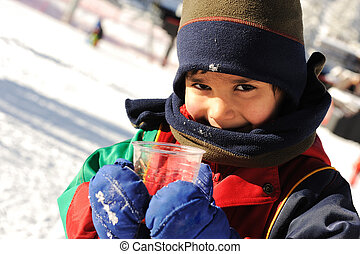 Happy boy on snow, drinking hot tea and smiling