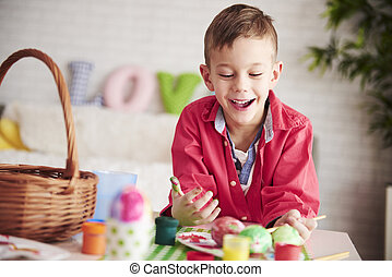 Happy boy painting eggs for Easter