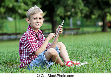 happy boy play with tablet pc in park