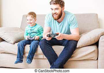 Happy boy playing computer games with his father at home