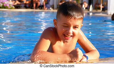 Happy Boy Playing in a Pool with Blue Water. Slow Motion