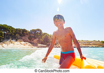 Happy boy playing in waves with inflatable float