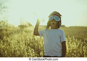 Happy Boy playing to be airplane pilot, funny guy with aviator cap and glasses, carries in his hand a plane made of paper