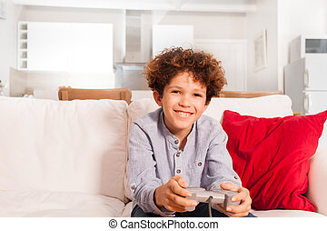 Happy boy playing video game with joystick at home