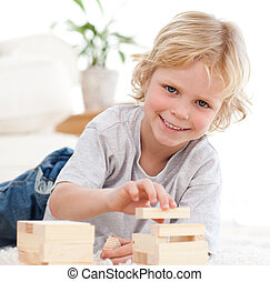 Happy boy playing with dominoes lying on the floor
