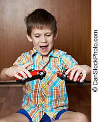 Happy boy playing with toy cars