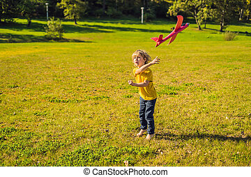 Happy boy playing with toy plane in the park