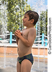 Happy Boy Playing with Water in Fountain in Public Ground in Summer Time