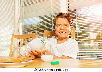 Happy boy pouring milk at breakfast in the kitchen