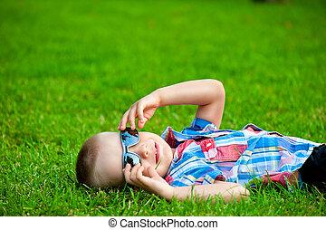 happy boy resting lying on green grass in sunglasses