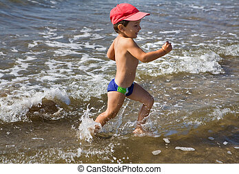 Happy boy running in water