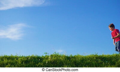 Happy boy running on green grass hill against blue sky