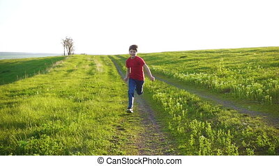 Happy boy running on rural road in green grass field