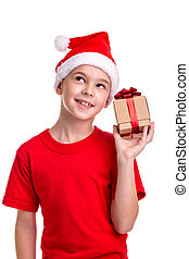 Happy boy, santa hat on his head, received the small gift box in the hand. Concept: christmas or Happy New Year holiday