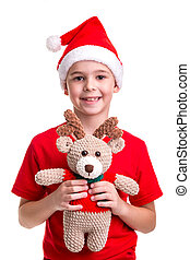 Happy boy, santa hat on his head, received the soft toy of deer. Concept: christmas or Happy New Year holiday