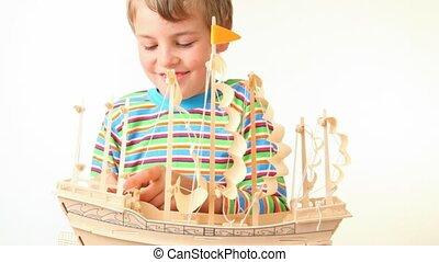 boy sets up sails of toy model of ship - happy boy sets up...