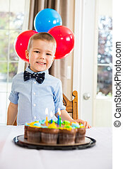 Happy Boy Sitting In Front Of Birthday Cake
