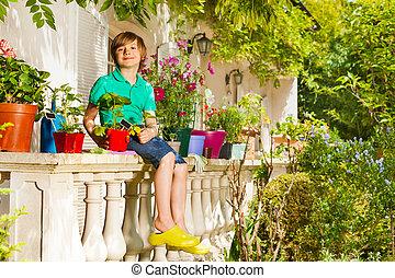 Happy boy sitting on balustrade of balcony garden
