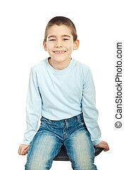 Happy boy sitting on chair