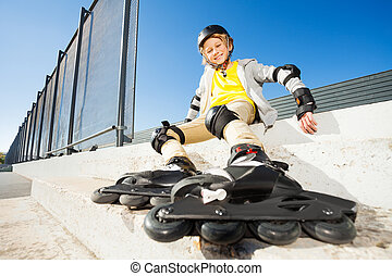 Happy boy sitting on the stairs in roller skates