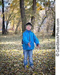 happy boy throws leaves in autumn Park