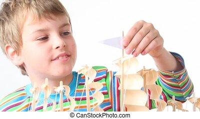boy touching wooden model of ship