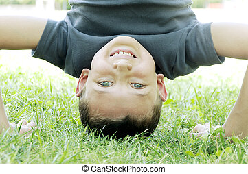 happy boy upside down on the grass