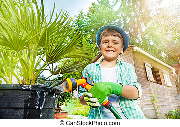 Happy boy watering palm tree using hand sprinkler - Close-up...