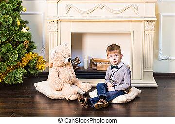 Happy boy with a teddy bear. Christmas tree. New Year