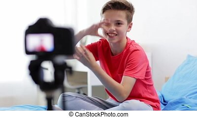 happy boy with camera recording video at home - blogging,...