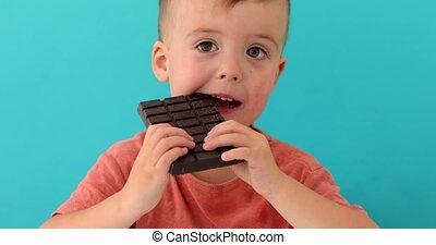 happy boy with chocolate bar - happy boy eating chocolate...