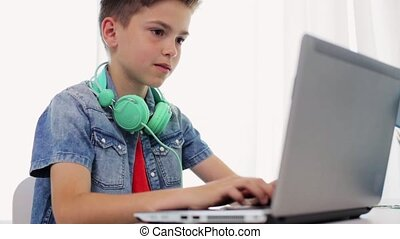 happy boy with headphones typing on laptop at home -...