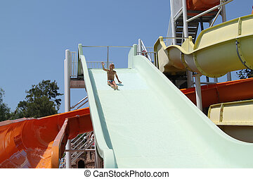 happy boy with his hand up flies out of water slide
