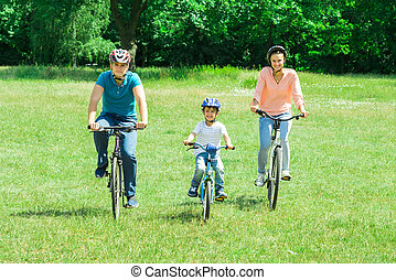 Boy With His Parent Riding Bicycle