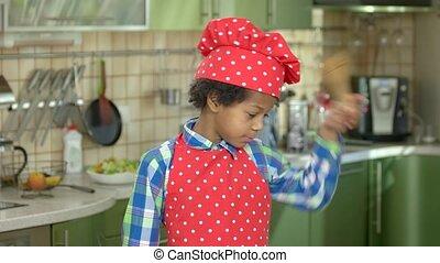 Happy boy with kitchen utensils. Child in chef uniform.