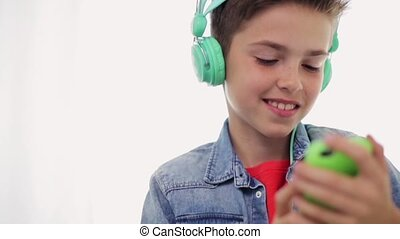 happy boy with smartphone and headphones at home