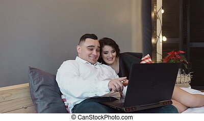 Happy boyfriend and girlfriend doing shopping online with laptop computer - Young people having fun buying presents in internet at home. Holidays and shopping concept