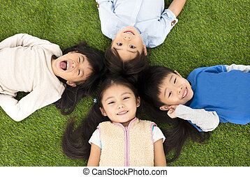happy boys and girls lying on green grass