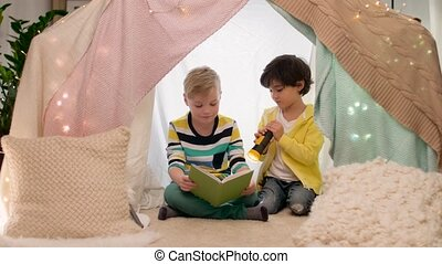 happy boys reading book in kids tent at home